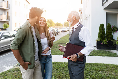 young couple talking to an agent and buying a new home